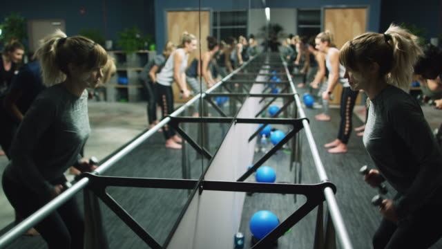 a group of caucasian women in their twenties perform back exercises with hand weights in a barre studio - barre stock videos & royalty-free footage