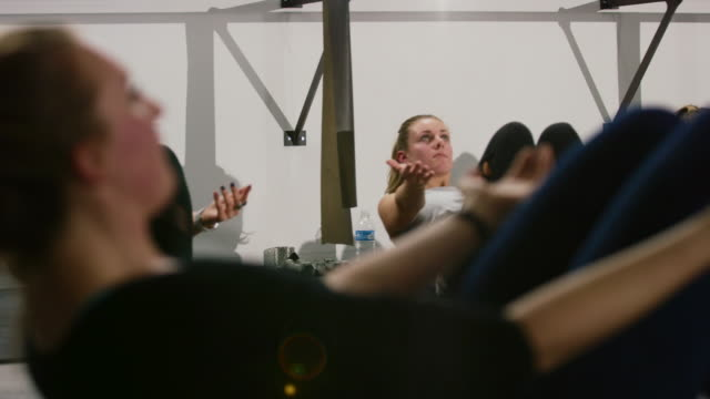 a group of caucasian women in their twenties performs leaning back sit-ups on fitness balls in a barre exercise studio - barre stock videos & royalty-free footage