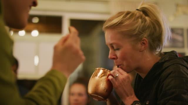 20 代の白人女性のグループはドリンクを飲みながら居心地の良い屋内設定で互いに話す - マグカップ点の映像素材/bロール