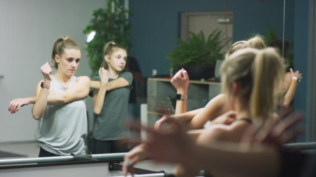 vídeos de stock, filmes e b-roll de um grupo de mulheres caucasianos de idades misturadas, para esticar os braços em um estúdio de barre - balé