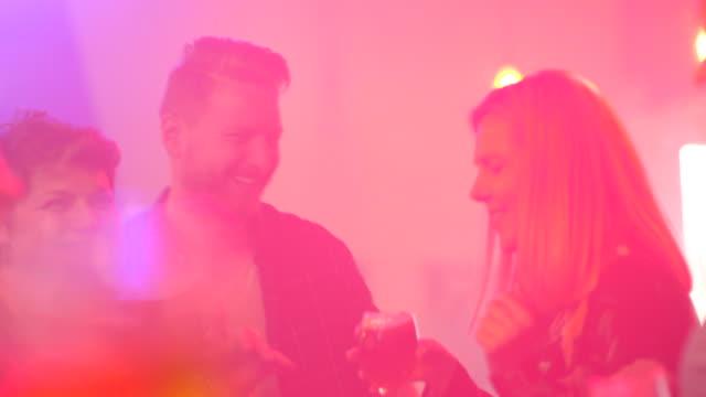 gruppe fröhlicher freunde tanzen in einem nachtclub - after work stock-videos und b-roll-filmmaterial