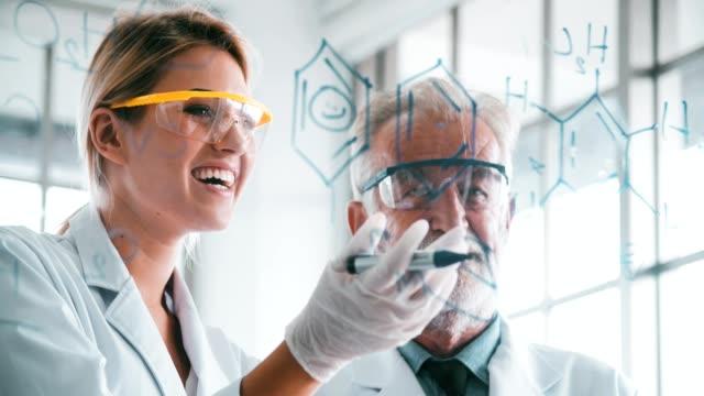 4k: gruppe von chemikern studium formel auf transparente board - transparent stock-videos und b-roll-filmmaterial