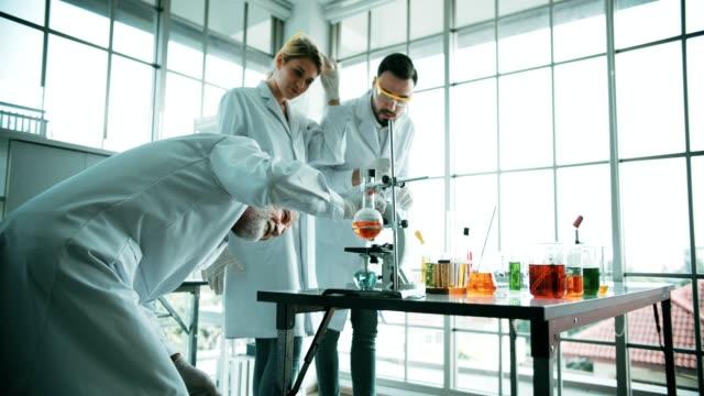 4k : group of chemists working in laboratory - vetreria da laboratorio video stock e b–roll
