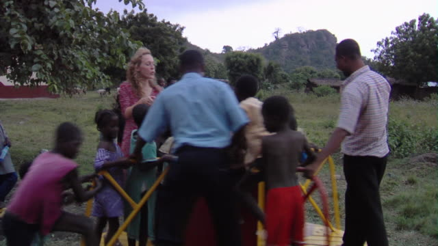 vidéos et rushes de ms group of children and adults playing on merry-go-round, tamale, ghana - village
