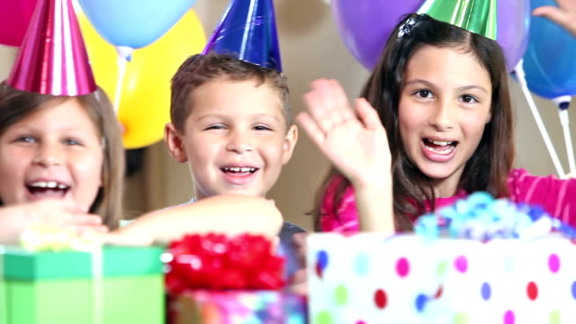 Group of children at a birthday party waving