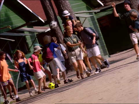 vídeos y material grabado en eventos de stock de canted group of children + camp counselors playing with a plastic disc, kicking soccer ball + jumping rope - cuerda de saltar