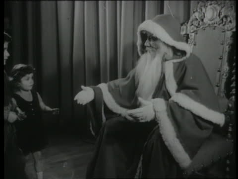b/w 1960 group of children come up to santa claus on throne - anno 1960 video stock e b–roll
