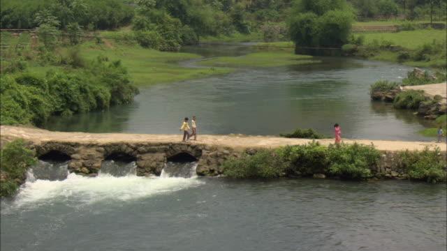 ws ha group of children crossing stone bridge, guilin, guangxi zhuang autonomous region, china - guangxi zhuang autonomous region china stock videos & royalty-free footage