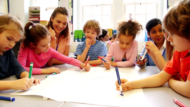 group of children drawing in class - insegnante video stock e b–roll