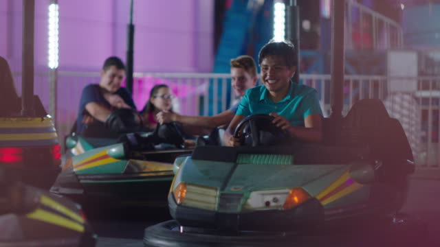 a group of children drive bumper cars at a summer carnival - gala stock videos & royalty-free footage