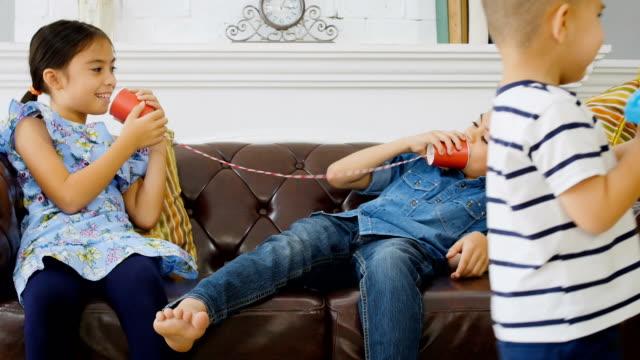 grupp barn avnjuter tenn kan ringa tillsammans i vardagsrummet hemma - sn�� bildbanksvideor och videomaterial från bakom kulisserna