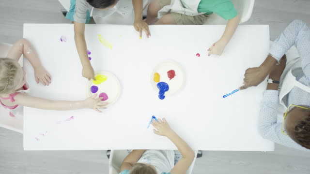 group of children finger-painting on a clean white table - disegno video stock e b–roll