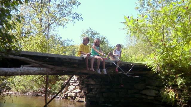 vídeos y material grabado en eventos de stock de ms, group of children (8-11) fishing sitting on wooden bridge, bovina, new york state, usa - descalzo