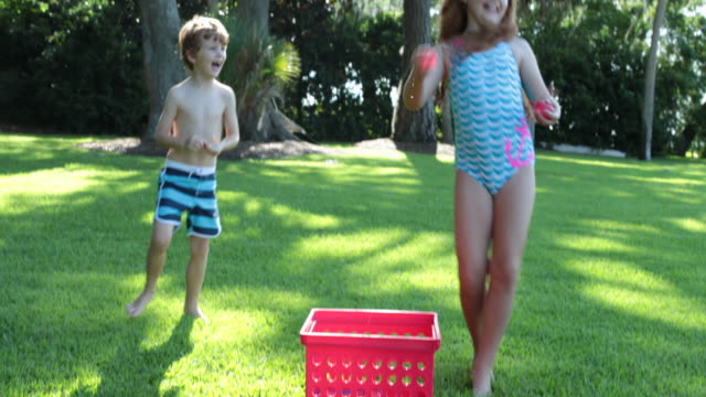 group of children having fun playing with water bombs in garden - swimming costume stock videos and b-roll footage
