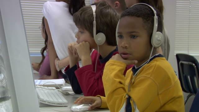 vidéos et rushes de cu, group of children (6-7, 8-9) in computer lab - main au menton