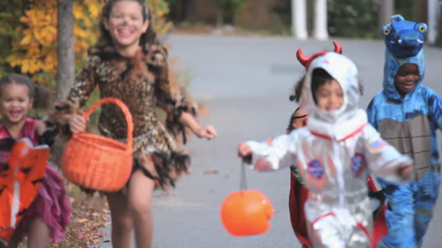 vídeos de stock, filmes e b-roll de ms pan group of children (2-7) in halloween costumes running down neighborhood street / richmond, virginia, usa. - fantasia disfarce