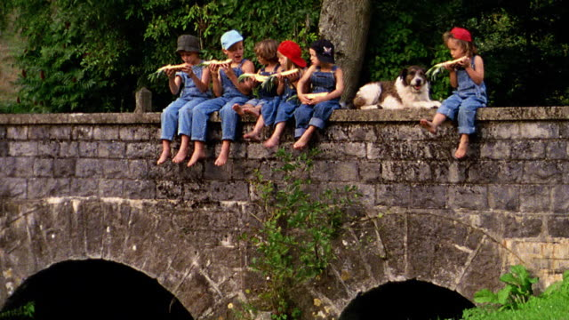 Group of children in overalls eating pineapple + kicking feet sitting with dog on bridge