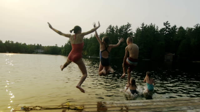 stockvideo's en b-roll-footage met group of children jumping off dock - pret