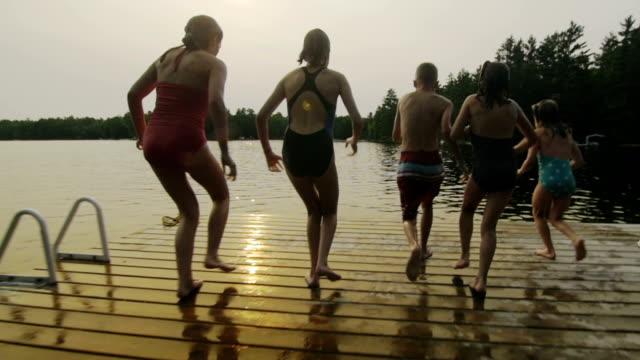 group of children jumping off dock - lake stock videos & royalty-free footage