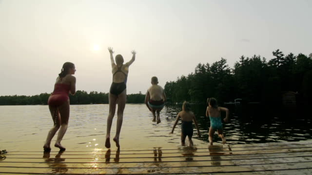 group of children jumping off dock - swimming stock videos & royalty-free footage