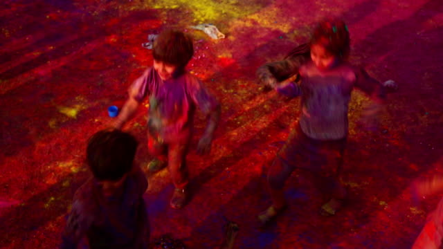 Group of children playing holi and dancing, Delhi, India
