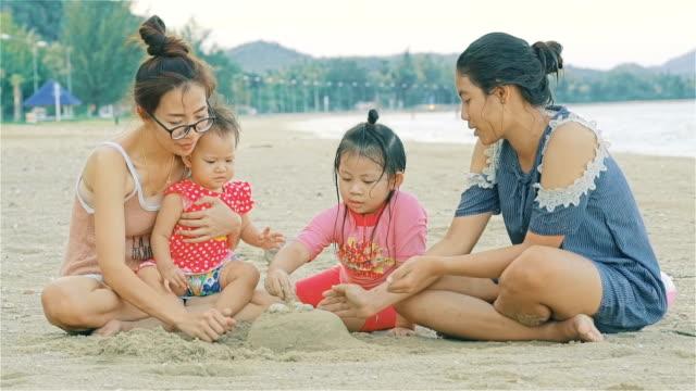 vidéos et rushes de groupe d'enfants qui jouent avec la jeune femme sur la plage - dimanche
