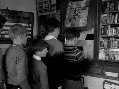 group of children queue up to buy tickets and sweets at a cinema kiosk. 1960. - ticket stock videos & royalty-free footage