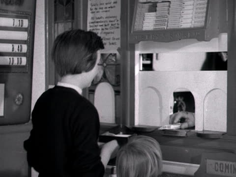 a group of children queue up to buy tickets and sweets at a cinema kiosk 1960 - film industry stock videos & royalty-free footage