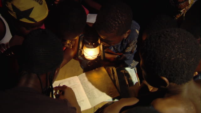 vidéos et rushes de slo mo cu ha group of children reading by oil lamp at night, tamale, ghana - lire