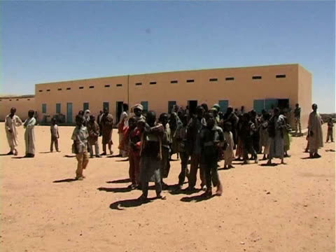 group of children standing outside school in desert / chad / audio - solo bambini maschi video stock e b–roll