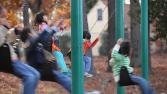 ms selective focus group of children swinging on swings on playground / richmond, virginia, usa - kinderspielplatz stock-videos und b-roll-filmmaterial