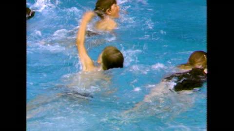stockvideo's en b-roll-footage met group of children take swimming lesson at uk summer camp; 1984 - swimwear