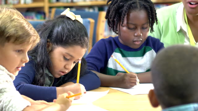 group of children, teacher, writing in library - 6 7 years stock videos & royalty-free footage