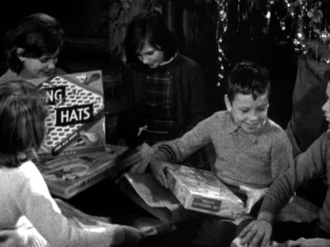 A group of children unwrap their Christmas presents 1961