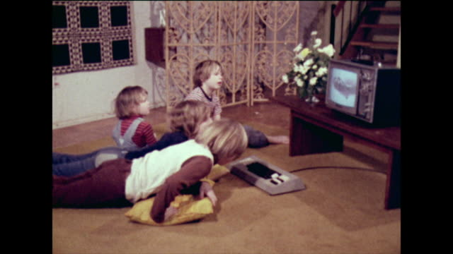vídeos de stock e filmes b-roll de group of children use the tv for homework; 1973. - parte de uma série