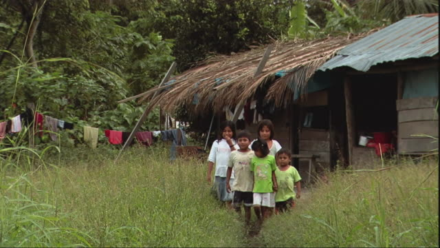 vidéos et rushes de ms group of children walking along village path, peru - cabane structure bâtie