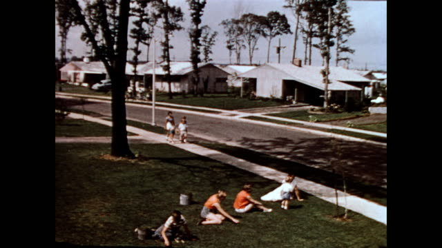 / group of children weeding in front yard as other group of kids walk by / view of the levittown streets levittown pa neighborhood streets on january... - ペンシルベニア州点の映像素材/bロール