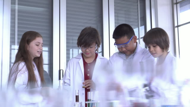 試験管前景を持つ子供のグループ - 発明家点の映像素材/bロール
