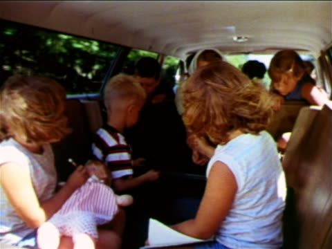 1965 group of children + woman riding in back seat + back of Ford station wagon / industrial