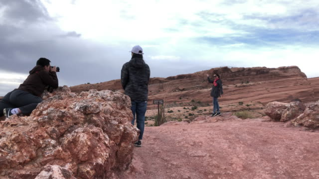 group of chinese tourists taking picture in arches national park - chinese language stock videos & royalty-free footage