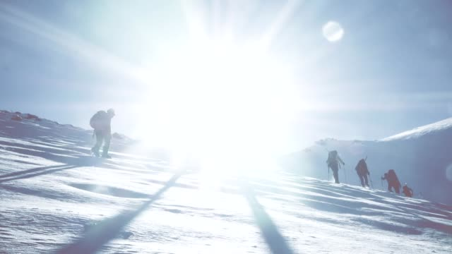 vídeos de stock e filmes b-roll de group of climbers are walking in the mountain peak - coberto de neve
