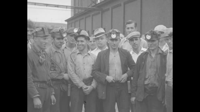 vidéos et rushes de a group of coal miners with helmets pose for photo then carry their lunch pails and enter the elevator to the mine / note exact day not known - mineur de charbon