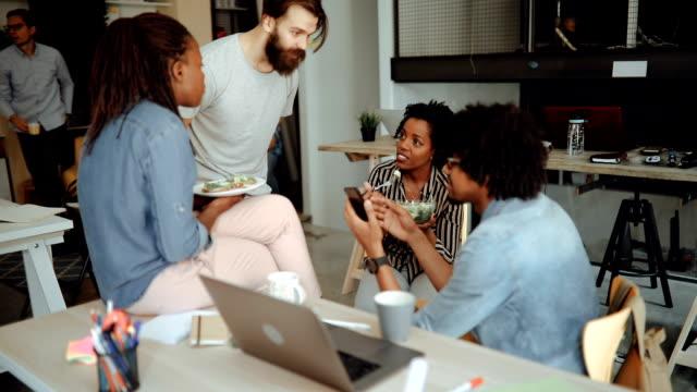 vidéos et rushes de groupe de collègues ayant le petit déjeuner au bureau - nouvelle entreprise