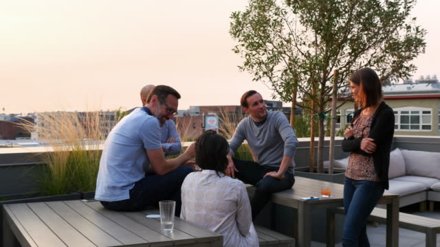 MS Group of colleagues having drinks after work on terrace of office building on summer evening