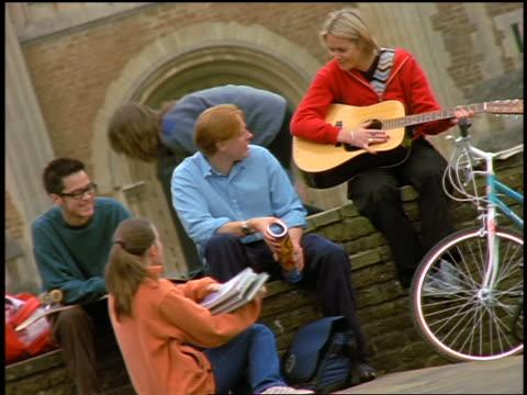 vídeos y material grabado en eventos de stock de group of college students sitting outdoors talking + playing guitar / england - 1990 1999