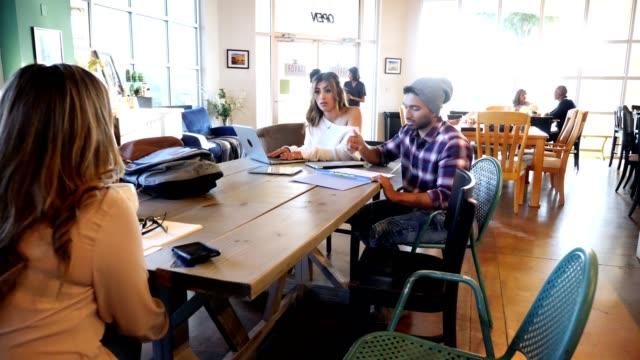 vidéos et rushes de groupe d'étudiants d'université étudiant dans le café à la mode - hipster personne