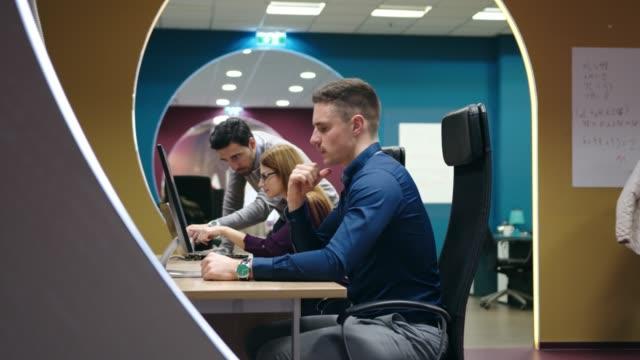 vídeos de stock, filmes e b-roll de grupo de programadores de computador sentados ao lado da mesa trabalhando em computadores - programador