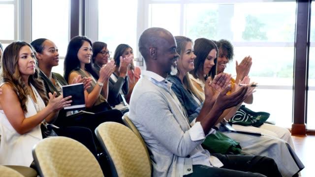 vídeos de stock e filmes b-roll de group of conference attendees applaud keynote speaker - conferência de negócios