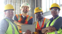 Group of construction workers looking at digital tablet