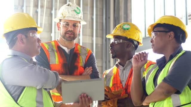 vídeos de stock, filmes e b-roll de grupo de trabalhadores da construção que olham a tabuleta digital - trabalhador manual
